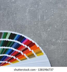 Color palette guide, fan, catalogue on grey background. Ral color fan on conсrete floor