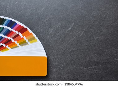 Color palette guide, fan, catalogue on  black background. Ral color fan  with yellow cover on conсrete texture