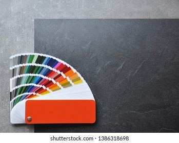 Color palette guide, fan, catalogue on grey and black background. Ral color fan  with orange cover on conсrete texture