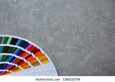 Color palette guide, fan, catalogue on grey background. Ral color fan  on conсrete texture