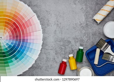 Color palette guide and painting accessories ( paint brushes, roller and cans of paint) on grey background. Top view with copy space,  Concept of construction or design office