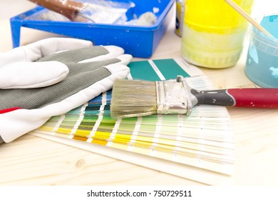 Color palette guide and painting supplies, paint brushes and color cans on wooden background