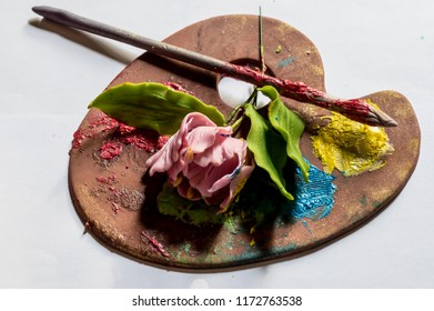 The color palette with rose and brush.