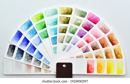 The color palette is a semicircle made of white watercolor paper with painted rectangles. Pantone fan lies on a white background. Various colors red, blue, green, yellow, metallic shades.
