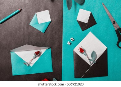 Color paper. Small colored envelopes. Workplace designer. Romantic letter. Flower arrangement with stationery items. Lead pencil, scissors, red roses lay on wooden background. Flat lay. Dice for luck