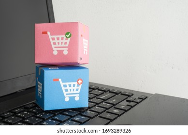 Color parcel carton box with shopping trolley cart logo on laptop computer with white wall background. E-commerce or online shopping, logistic inventory control, cash on delivery (COD), wfh concept.