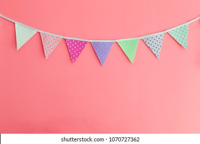 Color party bunting banner cotton triangle flag over red wall texture background