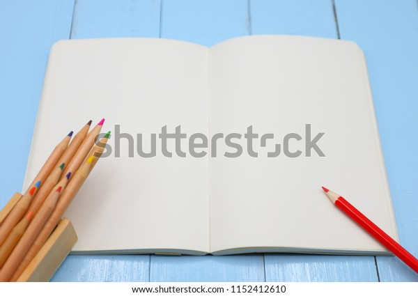 Color pencil on empty notebook plate, education and business concept at top view.