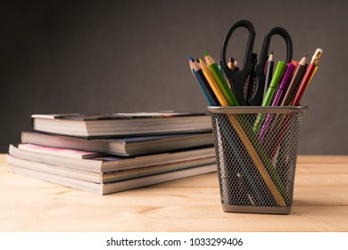 color pencil in pen pot and book on working desk