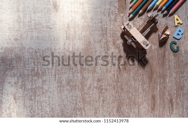 Color pencils, airplane toys model on wood background. ideal for back to school and education background.