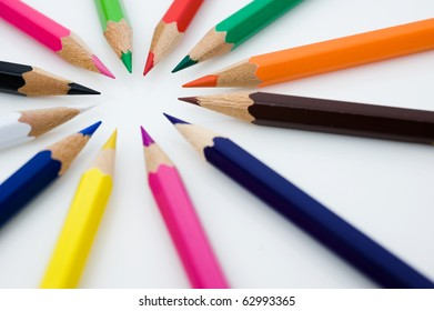Color pencils in arrange in color wheel colors on white background.
