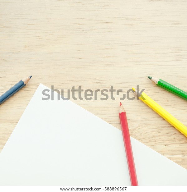 Color pencils and blank white paper on wood table