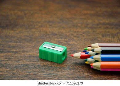 Color pencils with green sharpener on the wooden background, success concept, selective focus.