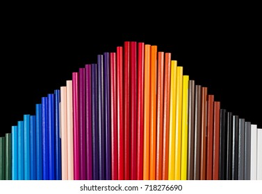 Color pencils isolated on black background in arc formation. Shot at close-up
