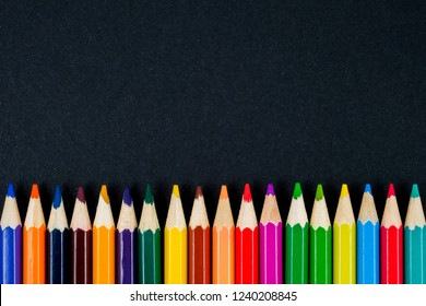 Color pencils on black background top view. Copy space.