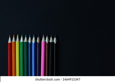 lot color pencils on black background, top view close up. back to school.