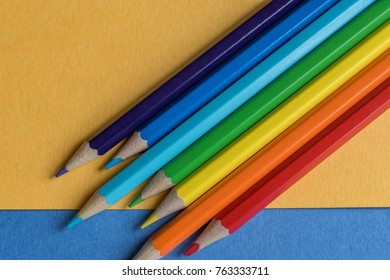 color pencils on blue and orange background. rainbow colors