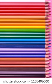 Color pencils on pink pastel background, close up. Set of colorful pencils, copy space. Crayons. Top view, flat lay. Back to school, college concept. Abstract background