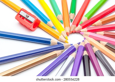 color pencils and an pencil sharper lying in a circle on a white background