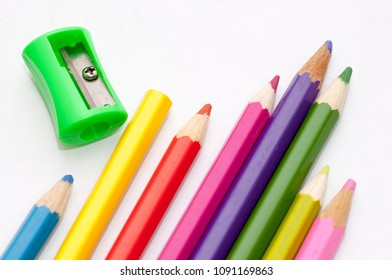 Color pencils and a sharpener on a white sheet of paper.