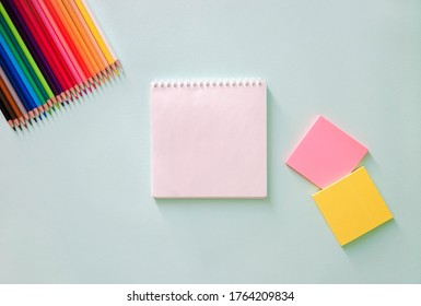 Color pencils, stationery stickers pink and lemon color and white clear sheet of note book on a light blue background. Horizontal photo. Flat lay minimalistic composition. Back to school, college