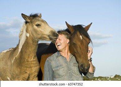 A color photo of a happy laughing forties man having fun and petting his two horses.