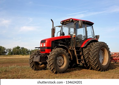 Color photo of a red tractor against the blue sky