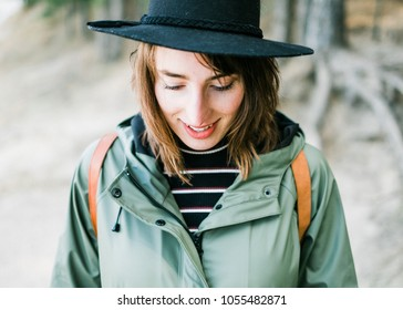 Color photo of a young woman with dark hair and a hat. She's walkig and standing next to a lake or river in the forest. A solo traveler wearing a raincoat and going on an adventure