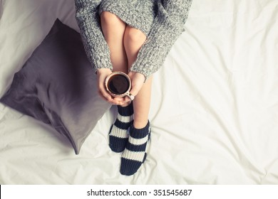 Color picture of a beautiful young woman drinking coffee at home in her bed wearing a cozy sweater