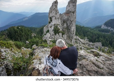 Color picture of an elderly couple embracing on top of a mountain