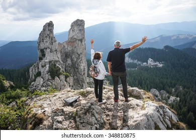 Color picture of an elderly couple holding hands and waving on top of a mountain