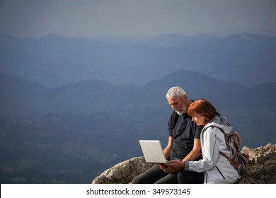 Color picture of an elderly couple using a laptop on top of a mountain