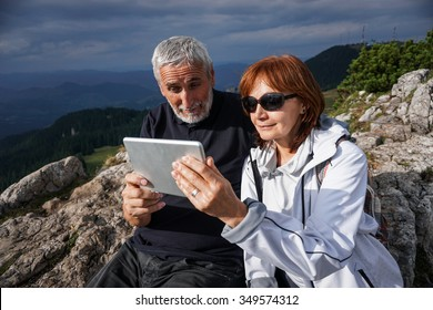 Color picture of an elderly couple using a tablet on top of a mountain