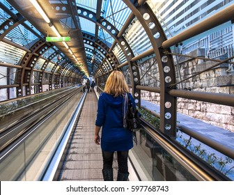 Color picture of a moving sidewalk in a tunnel with anonymous blonde girl