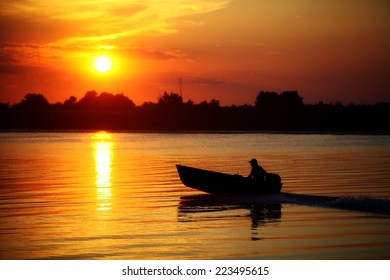 Color picture of people in a boat on a river at sunset.
