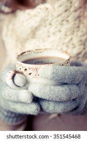 Color picture of a young beautiful woman in mittens holding a cup of coffee
