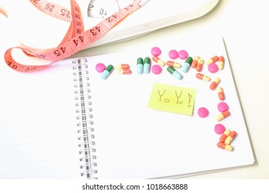 "Color pill on notebook with paper write word ""Yo Yo !"""