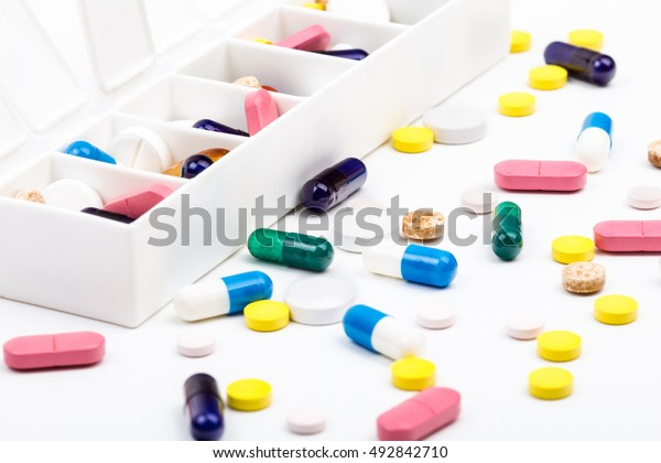 Color pills and capsules in and out of pill organizer landscape view