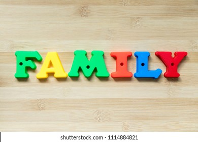 Color plastic alphabet in word family on wood background