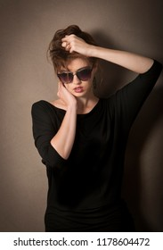 Color portrait of edgy woman dressed in black with sunglasses, holding her brunette hair while leaning against a wall.
