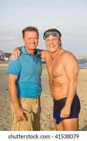 A color portrait of a happy laughing gay couple standing on the beach.