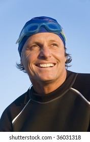 A color portrait of a happy smiling man wearing a wetsuit,goggles and cap