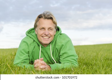 A color portrait photo of a happy smiling blond haired man in his forties laying on the green grass wearing a green colored top.