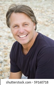 A color portrait photo of a happy smiling man in his forties looking straight at camera.