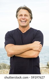 A color portrait photo of a happy smiling man in his forties standing on the beach