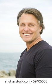 A color portrait photo of a happy smiling man in his forties at the beach.