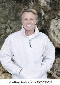 A color portrait photo of a happy smiling mature blonde man in his forties wearing a white fleece top and giving a warm friendly look towards the camera.