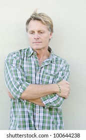 A color portrait photo of a pensive and sad looking mature man in his forties wearing a green checked shirt.