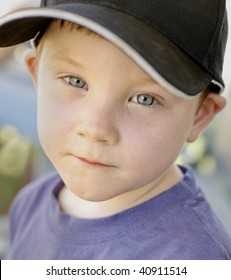 Color portrait of very cute four year old boy with blue eyes wearing a black baseball cap