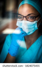 Color portrait of a young female medic by a window, wearing a mask and glasses, illustration for the coronavirus Covid-19 pandemic.